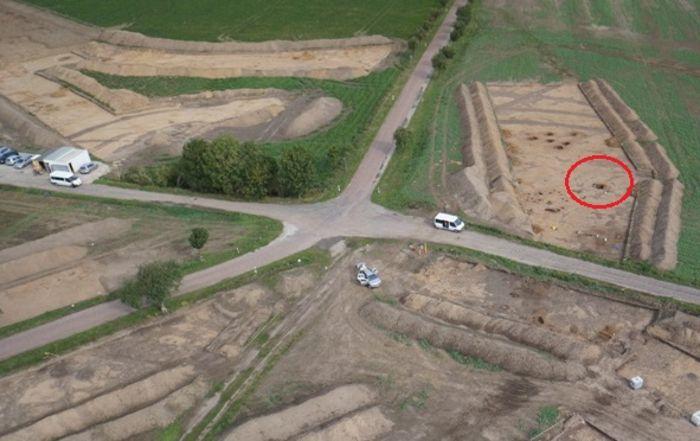 Abb. 9: Libehna, Fundstelle 8. Grube Befund 2030 im Inneren des Erdwerks (roter Kreis), nördlich davon befinden sich weitere Gruben dieser Zeitstellung (Blick nach Nord). Im Hintergrund sind die drei parallel verlaufenden Gräben des Erdwerks zu erkennen. Auf der linken Bildseite tauchen zwei der Gräben hinter den Containern wieder auf. Andreas Poppe, Fa. Geo-Metrik Ingenieurgesellschaft mbH Magdeburg, modifiziert durch Andrea Moser.