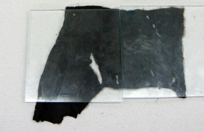 Abb. 2: Lederfragment von Abb. 1 nach der Tränkung mit PEG 600, auf Zellstoff ausgebreitet und mit Glasplatten beschwert. © Landesamt für Denkmalpflege und Archäologie Sachsen-Anhalt, Heiko Breuer.