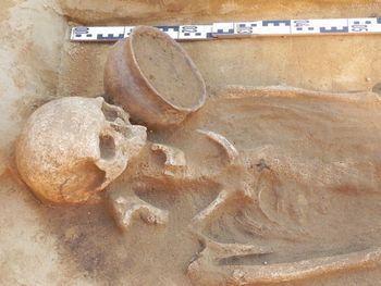 Abb. 3: Konischer unverzierter Keramiktopf neben dem Kopf einer Greisin. © Landesamt für Denkmalpflege und Archäologie Sachsen-Anhalt.