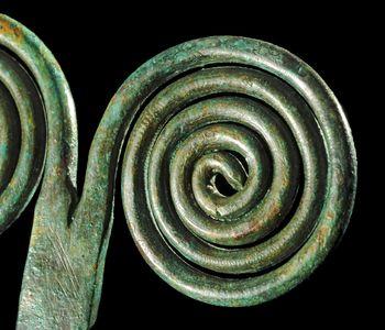 Abb. 4: Das Detail der Brillennadel zeigt die geritzten Verzierungen auf den Spiralen und Schleifspuren auf dem verbreiterten Schaft. © Landesamt für Denkmalpflege und Archäologie Sachsen-Anhalt, Andrea Hörentrup.