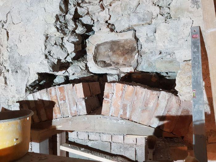 Abb. 11: Die Rückseite der Inschriftentafel oberhalb des Segmentbogens war bis zu den Sanierungsarbeiten nicht zu erkennen. Ursprünglich hinter Steinen verborgen, zeigte sich eine Mulde mit Resten aus Heu und Stroh. Darin lagen die beiden verschlossenen Flaschen bis dahin unentdeckt. © Christian Schirbel.