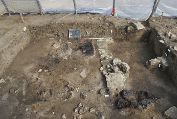 Abb. 3b: Unter einer massiven Brandschicht (Abb. 3a) konnten Mauerfundamente und verkohlte Holzkonstruktionsteile dokumentiert werden. © Landesamt für Denkmalpflege und Archäologie Sachsen-Anhalt.