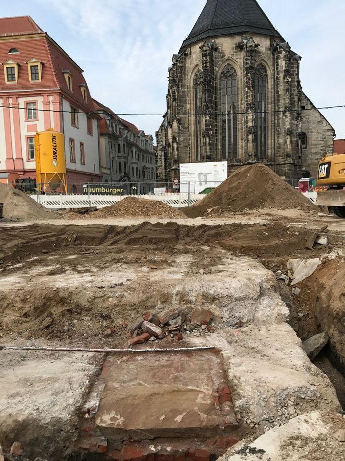 Abb. 3: Fundament mit Grundstein während der Freilegung. Im Hintergrund ist die Marienkirche am Marktplatz zu sehen. Gegenüber von ihr, war das Denkmal am 18. August 1900 eingeweiht worden. © Landesamt für Denkmalpflege und Archäologie Sachsen-Anhalt, Madeleine Fröhlich.