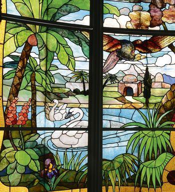 Abb. 1: Detail der farbenprächtigen Fenstergestaltung im Wintergarten mit exotischer Landschaft im orientalisch-tropischen Stil.  © Landesamt für Denkmalpflege und Archäologie Sachsen-Anhalt, Gunnar Preuß.